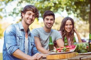 amigos felizes no parque almoçando foto