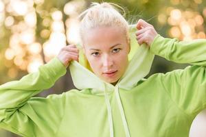 mulher confiante e desportiva com capuz verde na moda. foto