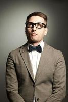 nerd confiante em óculos e gravata borboleta foto