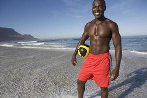 homem segurando futebol na praia foto