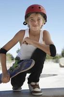 menino com skate agachado na pista de skate