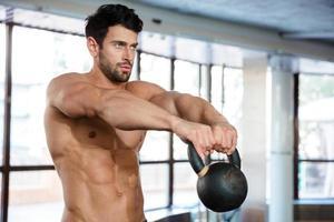 treino de homem musculoso com bola de chaleira foto