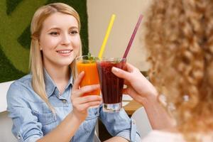 duas mulheres a tilintar de copos com cocktails no café foto
