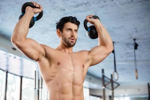 fitness homem levantando uma bola de chaleira foto