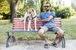 jovem com seu cachorro sentado em um banco de parque foto