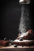 polvilhando brownie de chocolate com açúcar de confeiteiro vertical foto