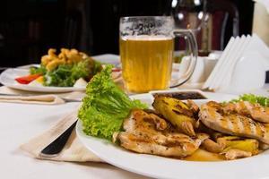 pratos apetitosos e caneca de cerveja na mesa foto