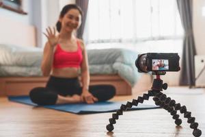 câmera gravando vídeo de mulher asiática praticando ioga foto