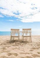 cadeiras brancas e mesa na praia foto