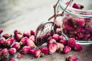chá de botões de rosa, infusor de chá e frasco de vidro.