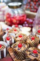 cupcakes frescos com cobertura de cereja e outros petiscos foto