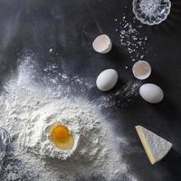 massa na mesa preta com farinha e ingredientes