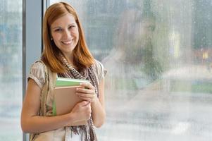 estudante com livros à janela foto