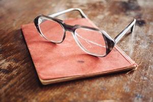 óculos vintage em livro antigo foto
