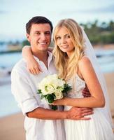 noiva e noivo ao pôr do sol na praia tropical