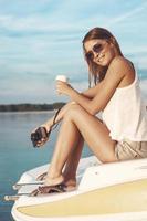 mulher barco sorrindo feliz olhando o mar