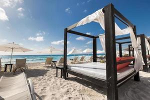 espreguiçadeiras luxuosas de madeira na praia do caribe foto