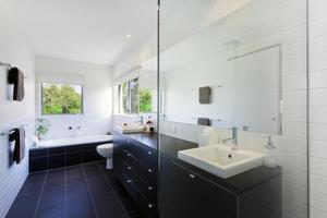 um banheiro limpo e moderno com azulejos escuros e paredes brancas foto