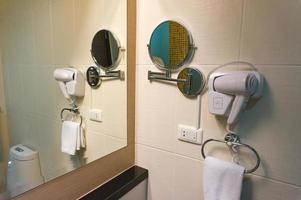 secador de cabelo branco e espelho na parede do banheiro foto