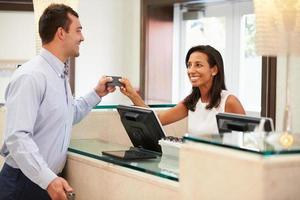 homem fazendo check-in na recepção do hotel foto