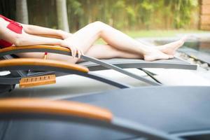 menina elegante em traje de banho deitada na espreguiçadeira. foto