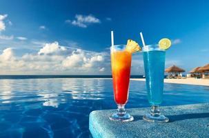uma laranja e um coquetel azul na beira de uma piscina