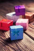 pequenas caixas de presente coloridas com fundo de madeira foto