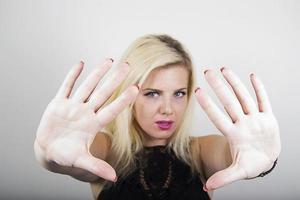 jovem mostrando o sinal pare com as mãos