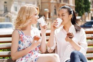 duas namoradas no parque com café e cupcakes foto