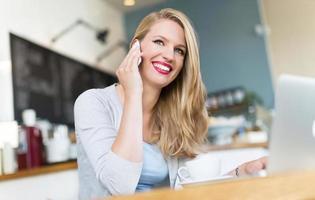 mulher usando telefone celular em um café foto