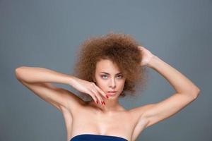 linda mulher atraente e confiante posando em fundo cinza foto