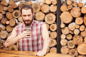 cara barbudo alegre está descansando em bar foto