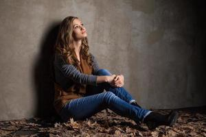 jovem de jeans com folhas de outono foto