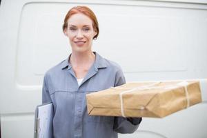 motorista de entrega sorrindo para a câmera por sua van segurando a parcela foto