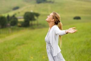 mulher com os braços estendidos no campo