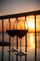 duas taças com vinho tinto ao pôr do sol