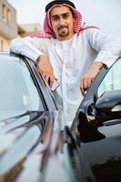 jovem árabe ao lado do carro
