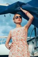 menina loira com vestido florido e óculos escuros segurando velas de barco foto