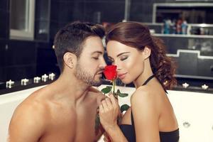 casal cheira rosa na banheira de hidromassagem foto