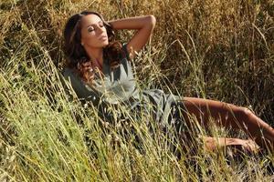 mulher com cabelo escuro posando em campo de verão
