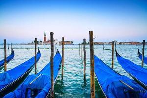 Veneza, gôndolas ou gondole no pôr do sol e igreja no fundo.