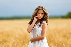 jovem linda em um campo de trigo foto