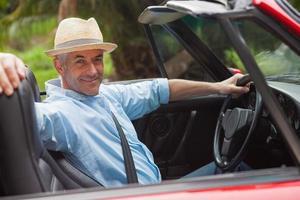 homem bonito sorridente posando em conversível vermelho