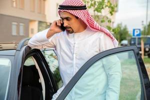 jovem árabe ao lado do carro foto