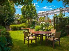 mesa de jantar posta em jardim exuberante
