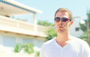 homem bonito de óculos, fumando ao ar livre. foto