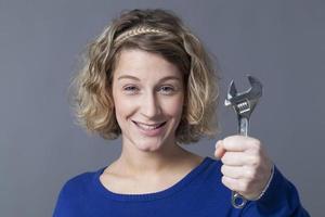 sorridente garota mecânica segurando uma chave para se divertir consertando carros