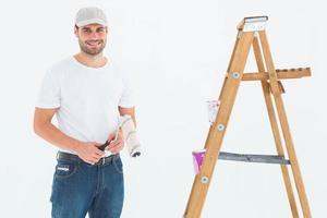homem segurando rolo de pintura enquanto está parado perto da escada