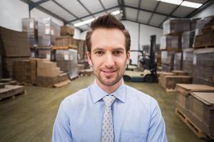 sorrindo gerente masculino no armazém foto