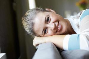 mulher sorridente relaxando no sofá foto